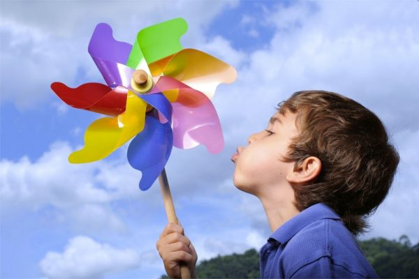 Cute kid playing with pinwheel